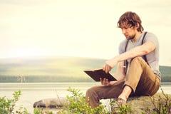 Läsebok för ung man som är utomhus- med den scandinavian sjön på bakgrund royaltyfri bild