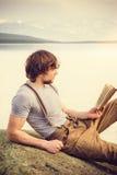 Läsebok för ung man som är utomhus- med den scandinavian sjön på bakgrund arkivbild