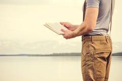 Läsebok för ung man som är utomhus- med den scandinavian sjön på bakgrund arkivfoton