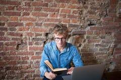 Läsebok för ung man som sitter med bärbar datordatoren i gillestuga arkivfoton