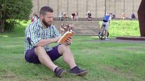 Läsebok för ung man som sitter på gräs steadicam lager videofilmer