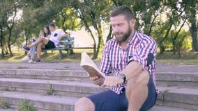 Läsebok för ung man som sitter på trappa lager videofilmer