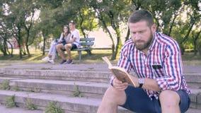 Läsebok för ung man som sitter på trappa glidareskott arkivfilmer