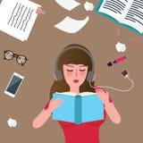 Läsebok för unga kvinnor och lyssnande musik på golv Arkivfoton