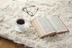 Läsebok med kaffe på matta royaltyfria bilder