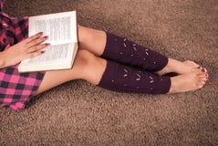 Läsebok och ben för ung kvinna med värmeapparater på mattgolv close upp royaltyfria foton