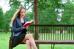 Läseboken för den tonårs- flickan parkerar in Arkivfoto