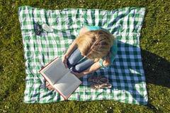 Läseboken för den unga kvinnan parkerar in, sett från över arkivbild
