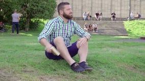 Läseboken för den unga mannen och kopplar av och att sitta på gräs steadicam lager videofilmer