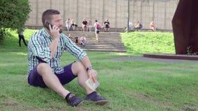 Läseboken för den unga mannen svarar påringningen som sitter på gräs steadicam arkivfilmer