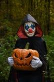 Läskig clown i skogen med en pumpa för allhelgonaafton royaltyfri bild