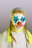 Läskig clown på en grå bakgrund Royaltyfri Fotografi