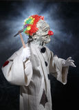 Läskig gigantisk clown med hammaren Arkivfoton