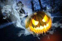 Läskig halloween pumpa på kyrkogård på natten Arkivbild