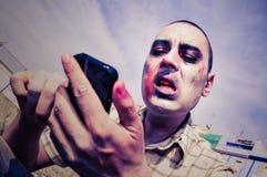 Läskig levande död som använder en smartphone, med en filtereffekt Arkivbilder