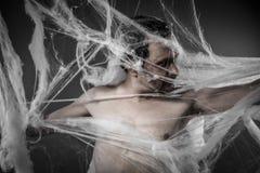 Läskig network.man trasslade till i enorm vit spindelrengöringsduk Arkivfoton