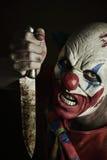 Läskig ond clown med en kniv royaltyfri bild