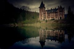 Läskig sikt av en slott med en sjö och reflexionen i skogen arkivfoton