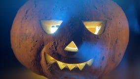 Läskig sniden halloween pumpa Slut upp av en framsida för stålar-nolla-lykta ` s i dimmiga skuggor arkivfilmer