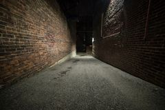 Läskig tom mörk gränd med tegelstenväggar arkivbilder