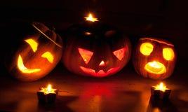 Läskiga halloween pumpa- och melonstålar-nolla-lyktor på svart bakgrund tände med små runda- och stjärnastearinljus Royaltyfria Bilder