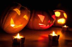 Läskiga halloween pumpa- och melonstålar-nolla-lyktor på svart bakgrund tände med små runda- och stjärnastearinljus Arkivbilder