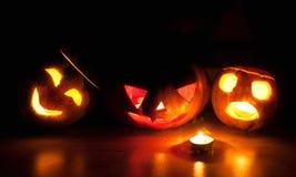 Läskiga halloween pumpa- och melonstålar-nolla-lyktor på svart bakgrund tände med små runda- och stjärnastearinljus Royaltyfri Fotografi