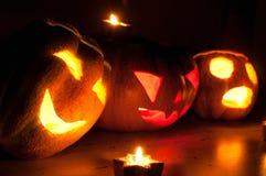 Läskiga halloween pumpa- och melonstålar-nolla-lyktor på svart bakgrund tände med små runda- och stjärnastearinljus Arkivbild