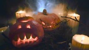Läskiga halloween pumpor i mörk skog med stearinljus stock video