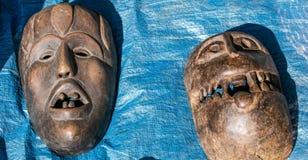 Läskiga sned afrikanska trämaskeringar på försäljningen för samling Arkivbilder