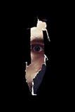 Läskigt öga av en man som spionerar till och med ett hål i väggen Royaltyfri Foto
