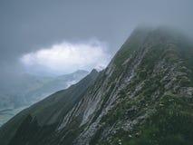 Läskigt brant berglandskap som täckas i för fjällängbrienzer för dimma schweizisk rothorn Schweiz arkivfoto