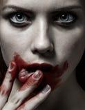 Läskigt flicka- och allhelgonaaftontema: stående av en galen flicka med en blodig framsida i studion Arkivfoton