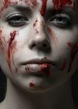 Läskigt flicka- och allhelgonaaftontema: stående av en galen flicka med en blodig framsida i studion arkivfoto