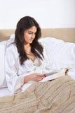 Läsning bokar på säng Royaltyfria Bilder