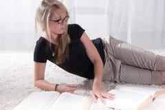 Läsning för kvinnlig student för stående ung i böcker Arkivbild