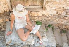 Läsning för trendig kvinna i en gammal stad arkivfoton