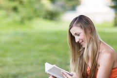 Läsning för ung kvinna i parkera Arkivfoto