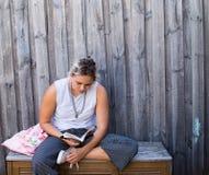 Läsning för ung kvinna på träbänk Arkivfoton