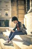 Läsning för ung kvinna på trappan royaltyfria bilder