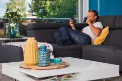 Läsning för ung man från en ebookavläsare, medan dricka kaffe på soffan royaltyfri bild