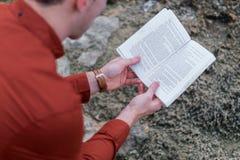 Läsning för ung man på kust Royaltyfria Foton