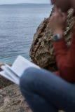 Läsning för ung man på kust Royaltyfri Bild