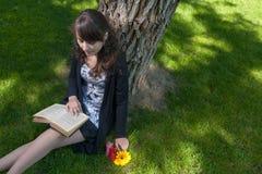 Läsning i parkera Gulligt flickasammanträde på gräs och som läser en gammal bok Arkivfoto