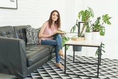 Läsning utbildning, kultur, folkbegrepp - den unga studentkvinnan läser en bok, medan hon sitter på soffan i a arkivbilder
