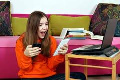 Läsninggoda nyheter för tonårs- flicka från meddelanden på smartphonen fotografering för bildbyråer