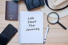 Lässt Anfang das joueney Wort auf Notizbuch mit Zusätzen, Kamera, Pass-, Vergrößern, intelligentemtelefon und Hut auf Holztisch,  lizenzfreie stockbilder
