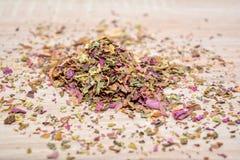 Lässt den Amaranttee, zerstreut auf dem Holztisch Hügel des Tees Lizenzfreies Stockbild