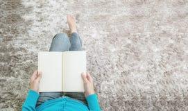 Läste den asiatiska kvinnan för closeupen som sammanträde på grå färgmatta på golvet i huset texturerade bakgrund för, en bok kop Royaltyfri Foto