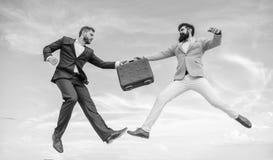Lätt avtalsaffär Affärsmän hoppar klipsk mitt- luft medan hållportföljen Fall med lönelyft din affär lyckat arkivbild